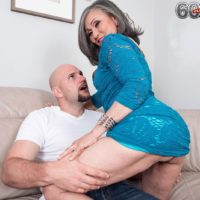 60 plus granny Kokie Del Coco seduces a younger man in a short dress on the couch