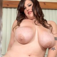 Brunette BBW Angel Sin sucks on a sex toy and nipples after removing sexy lingerie