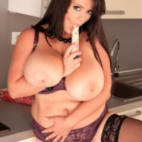 Brunette MILF Arianna Sinn sucks on a sex toy after unleashing huge tits in stockings
