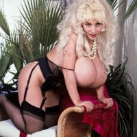 Famous pornstar Lulu Devine unleashes her giant boobs in sheer nylons and garters