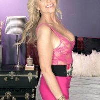 Hot mature woman Lauren Taylor seduces a younger man in a pink miniskirt