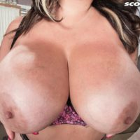 Tattooed brunette MILF Amaya May releases her giant tits from her bra in a miniskirt
