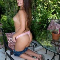 18 year old brunette Natalie Monroe strips to thong underwear on the patio in solo action