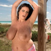 Brunette MILF Arianna Sinn flaunts her huge tits in the outdoors with the ocean in view