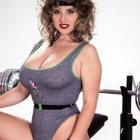 Famous older pornstar Tracy West uncorks her nice melons on home gym equipment