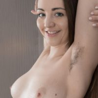 Flexible amateur model Cherry Bloom shows her furry armpits and hairy pussy in the nude