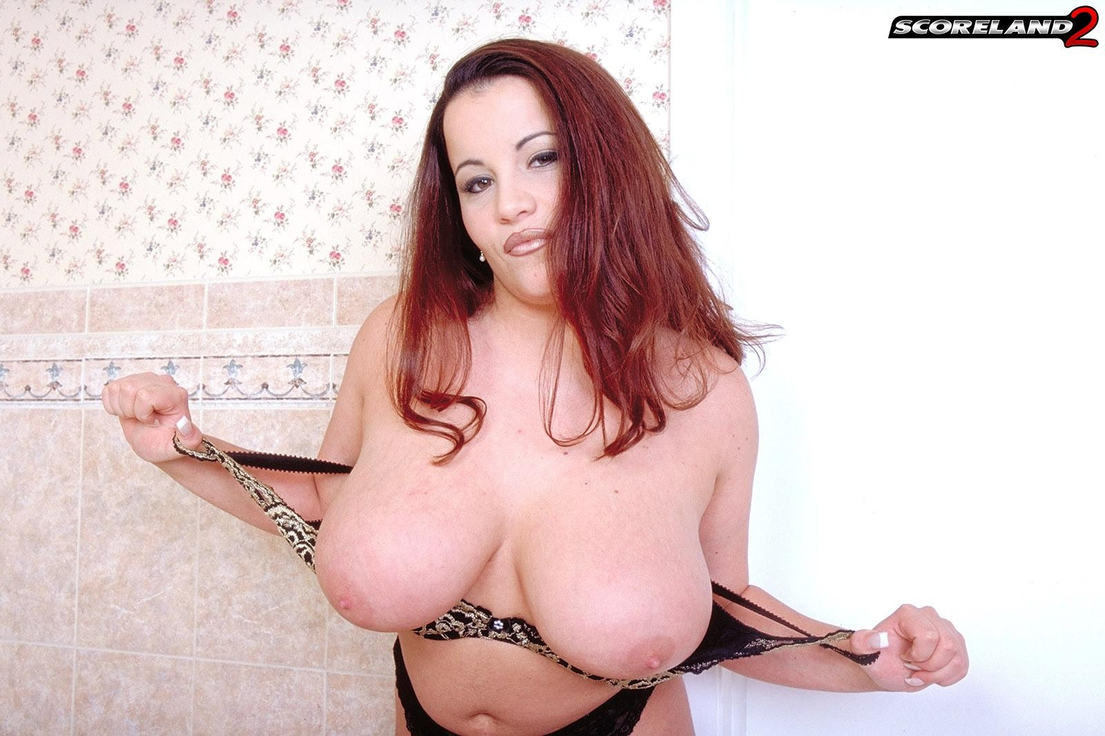 Redhead MILF Annie Swanson wets her huge boobs in the bathtub during solo action
