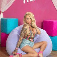 Tattooed blonde bombshell Bambi Blacks models non nude in bikini and cutoff shorts