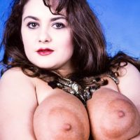 Solo model Justine licks the nipples of her big boobs attired in a garter