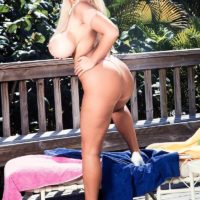 Blonde chick Honey Moons displays her tan lined knockers on the patio in heels