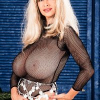 Blonde solo model Alexis Love holds her massive tits after freeing them from sheer top