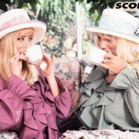Busty blonde Lisa Lipps and a gf of a similar description share a lesbian kiss in garden
