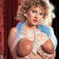 Curly blonde Suzanne Brecht exposes her giant boobs in lace lingerie and gloves