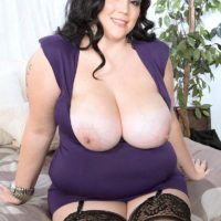 Dark haired BBW Charlotte Angel sets her giant tits free of dress and brassiere