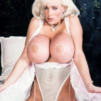 Famous pornstar Platinum Peaks holds her round boobs in a white bodysuit