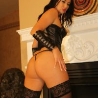 Hot brunette Mistress Ashley plays with her nipples in leather and stockings