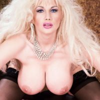 Natural blonde Jay Sweet displays her huge tits in a black thong and stockings