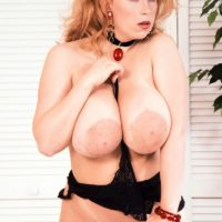 Natural redhead Tabatha Towers plays with her massive boobs in a choker and hosiery