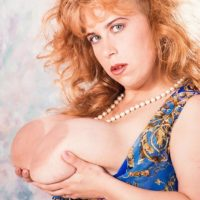 Redhead MILF Tabatha Towers unleashes her giant tits in over the knee nylons