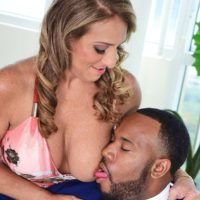 Sexy mature lady Torri Lee seduces a black man by freeing her big tits from her dress