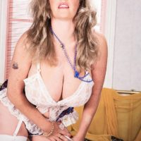 Solo girl Cathy Patrick unleashes her massive breasts in white nylons and garters