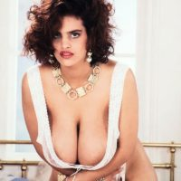 Solo model Nilli Willis grabs her giant boobs in white stockings and garters
