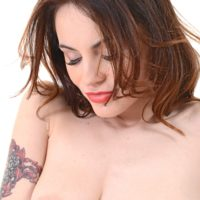 Tattooed solo girl Victoria Travel fingers her shaved pussy after stripping naked
