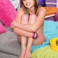 Cute teen Lizzy Bell uncovers her perky little tits as she gets naked atop her bed