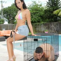 Dark haired wife Adriana Lily pegs her sissy over a dog cage on poolside patio