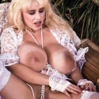 Famous pornstar Honey Moons unleashes her huge tits outdoors in garters and nylons