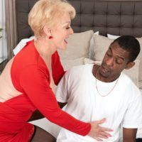 Busty blonde granny Seka Black holds a Peeping Tom's big black dick in her hand
