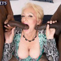 Sexy blonde granny Seka Black sucks on a couple of big black dicks during MMF sex