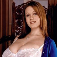 Solo model Nicole Peters licks a nipple after releasing her knockers from a brassiere