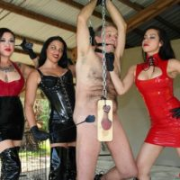 Cruel females with dark hair torment a male slave dressed in latex and long boots