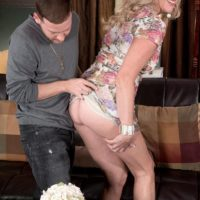 Mature blonde woman Val Kambel has her thong clad ass and a breast bared for her