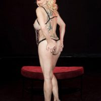 Older blonde Cammille Austin wears nipple clamps while modeling revealing lingerie
