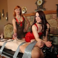 Clothed females Cheyenne and Amadahy tug on a restrained man's cock in latex wear