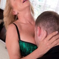 Hot blonde cougar Cali Houston is freed from sexy lingerie on a bed by her toy boy