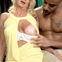 Hot blonde granny Nikki Chevious seduces a younger black man in a short dress
