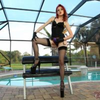 Pale redhead Deanna Winters poses on a bondage table in fetish wear and a strapon