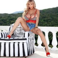 blonde solo model Venera sets her huge tits free on a balcony in cut off denim shorts