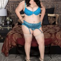 Dark haired BBW Charlotte Angel sets her huge boobs free of lingerie on top of a bed