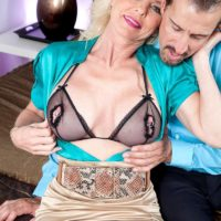 older blonde woman Cammille Austin seduces her lover in a tight skirt in the bedroom