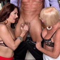 Mature women Renee Black and Scarlet Andrews take turns sucking a hard cock