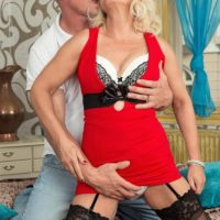 Older blonde woman Coco de Marq is freed from a red dress before sex with her younger lover