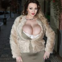 Sexy MILF Micky Bells sets her massive tits free off a tight fitting dress during solo action