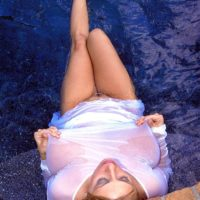 Solo model Autumn Jade shows off her large breasts in a body of water in see through clothing