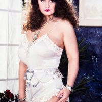 Thick solo model Justine sets her huge breasts free from a dress while wearing white stockings