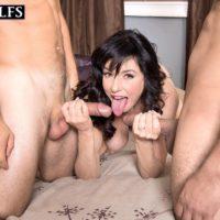 Busty older lady Karen Kougar tugs on two cocks after being caught masturbating