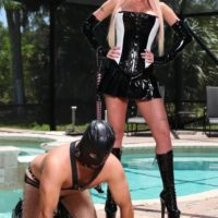 Hot blonde Alexia Jordon straddles atop a hooded male slave in latex attire and boots